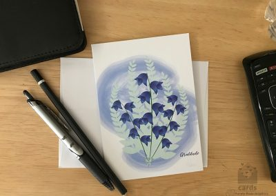 """Bluebell Flowers on a blue freeform background text on bottom right corner reads """"Gratitude"""""""