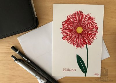 """red flower with green stem on white background, text on bottom left corner reads """"believe"""""""