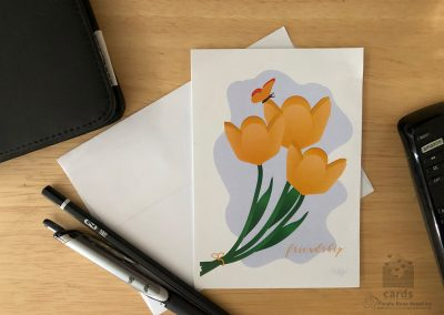 """tied yellow tulips with butterfly perched on center flower on freeform blue background, text on bottom right corner reads """"friendship"""" in script"""