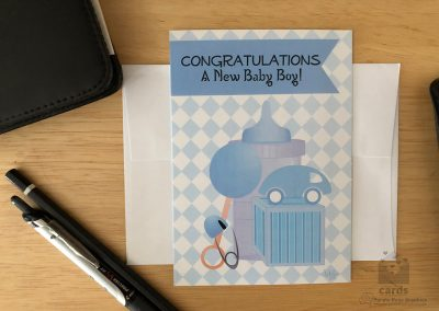 """blue baby bottle, rattle, diaper pin, block, toy car with diamond background. Text reads: """"Congratulations! A New Baby Boy!"""""""