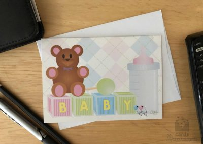 pink, blue and green baby blocks, green rattle, teddy bear, baby bottle and pink and blue diaper pins with pink and blue argyle background