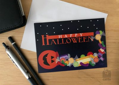 Black background with stars, orange text reading Happy Halloween with Jack O Lantern spilling candy along bottom of card