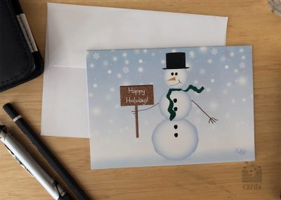 """Snowy Background with Snowman in Black top hat with carrot nose, coal features and buttons, and green scarf holding brown wooden sign that reads """"Happy Holidays"""""""