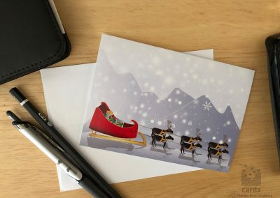 Holiday Card with Snow Falling in Front of Mountains with Red and Gold Sleigh pulled by Reindeer