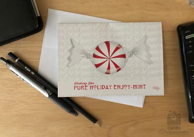 """White card with background pattern. Background pattern says """"celebrate"""" in pale gray script. Card features wrapped red and white stripped mint candy text on front says """"Wishing You Pure Holiday Enjoy-mint"""" with """"mint"""" pun for Enjoyment"""