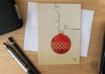 pale gold background with 3D drawn red and gold christmas bauble ornament on a green curling ribbon