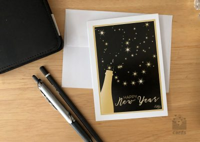 """Golden wine bottle spilling stars on to a gold framed black background. Text reads """"Happy New Year"""""""